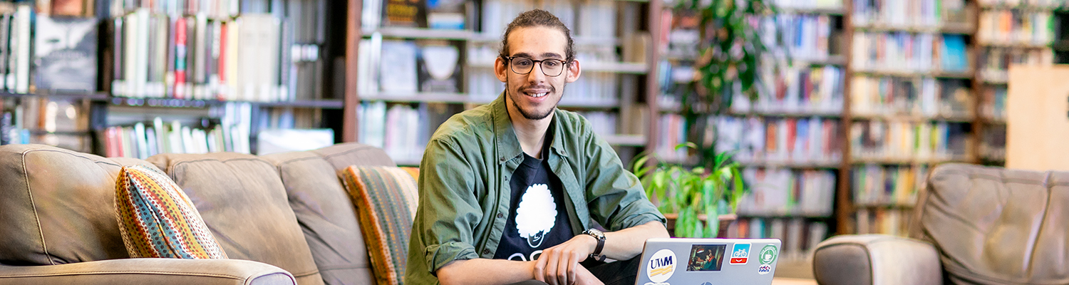 UWM student sitting in library with laptop