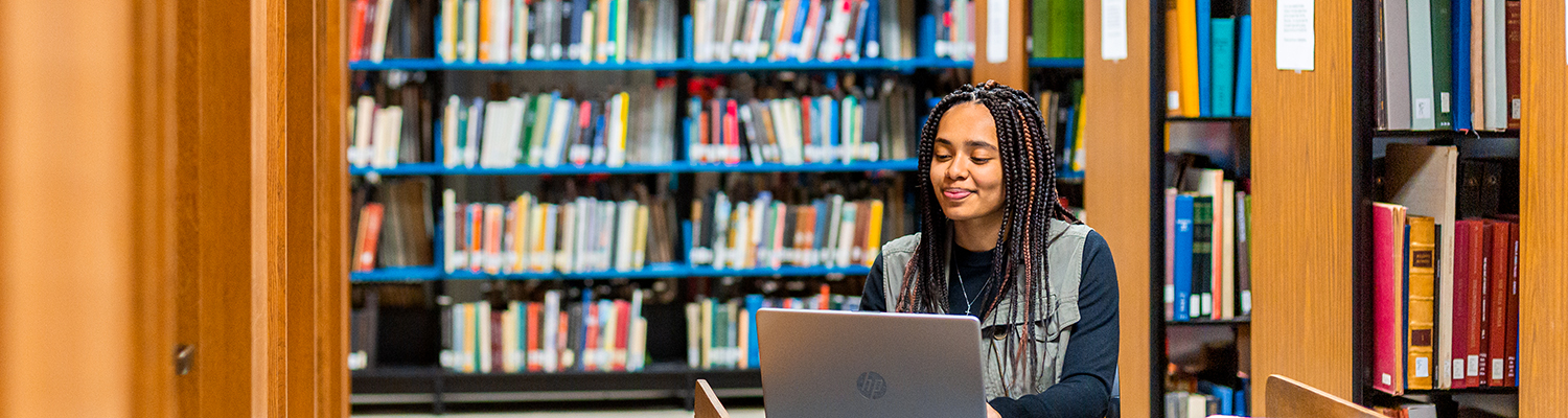 UWM student using laptop in library