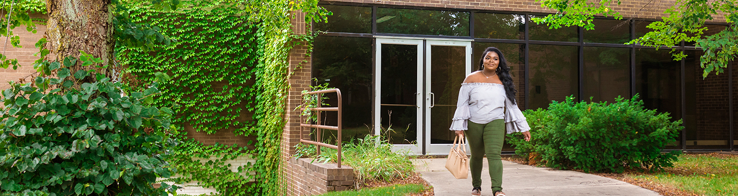 Wash Co student walking outside campus near greenery
