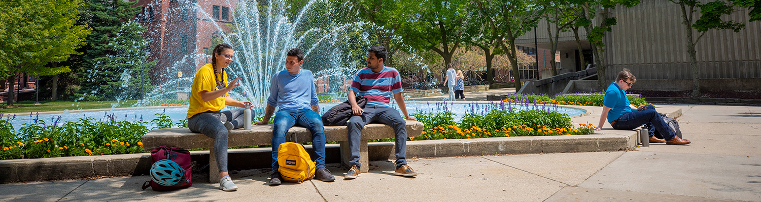 Students siting by the fountain on the main UWM campus.