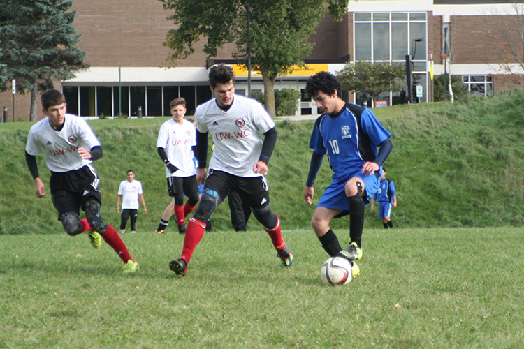 Soccer players in action on field in front of campus