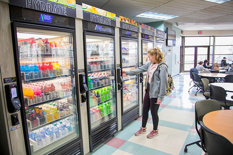 Female student looks at food items for sale behind glass doors in Smart Mart at UWM at Washington County