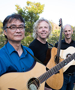 California Guitar Trio members stand outside with guitars