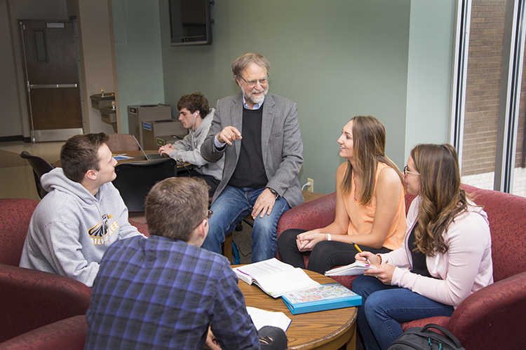 Professor talks with 4 students seated in one of breakout areas on Wash Cty campus