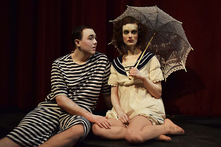 Two actors, male and female in white face pose - with woman (Eurydice) holding umbrella.