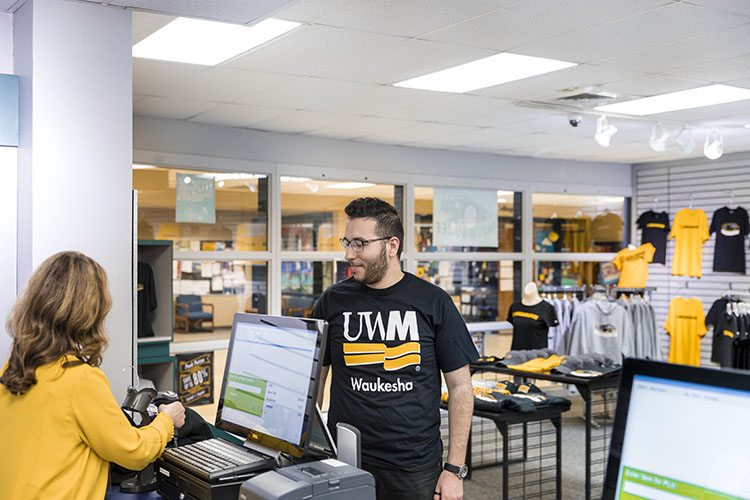 UWM at Waukesha student makes a purchase in campus bookstore. Shown at counter.