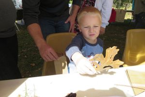 A child sits at a table, holding a fall leaf.
