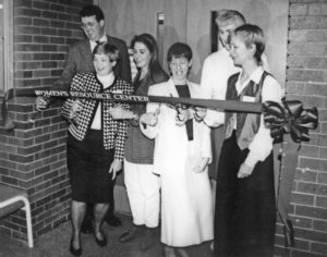a black-and-white photo of six people cutting a ribbon that reads Women's Resource Center